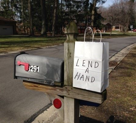 Mailbox with a bag of food on top that says Lend A Hand