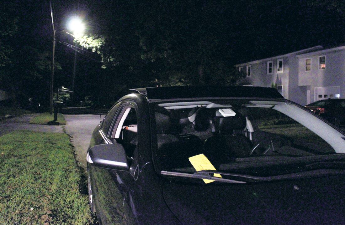 car parked on street at night with a ticket on the windshield